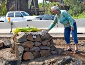 Aunty Puanani Rogers replaces a piece of coral at the kuahu, at the Mahunapu'uone Heiau at Wailua Beach February 2012