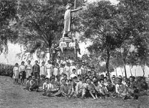 Kamehameha statue in Kapaʻau, with school children from plantation families, 1908
